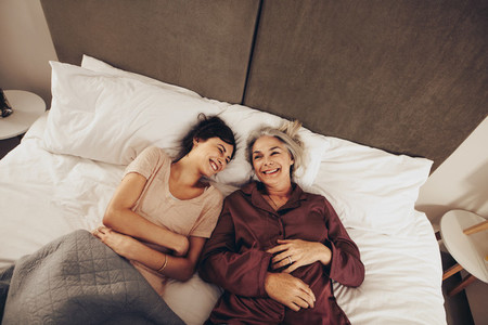 Top view of happy daughter and mother lying on bed at home
