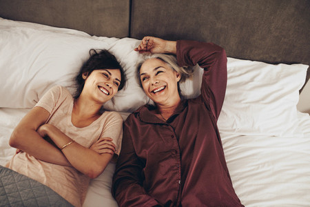 Happy mother and daughter lying on bed together and talking