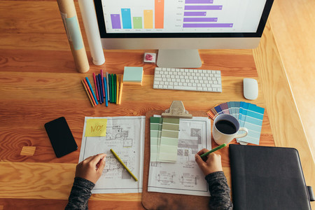Architect working over new blueprints at her desk