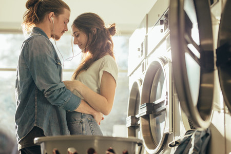 Couple standing in a laundry room holding each other