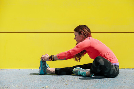 young woman stretching on a wall