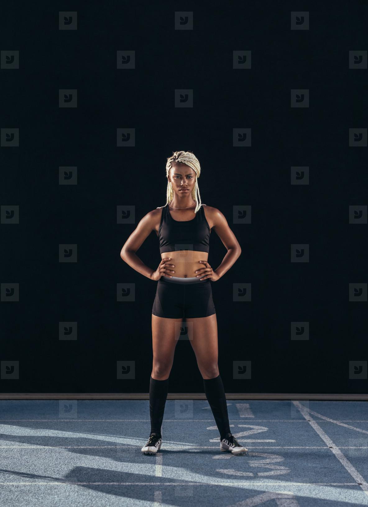 Female sprinter standing on a running track