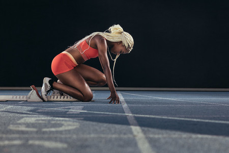 Sprinter using a starting block to start her sprint on a running