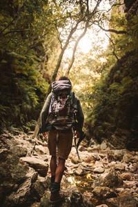 Man hiking through rough and rocky mountain trail
