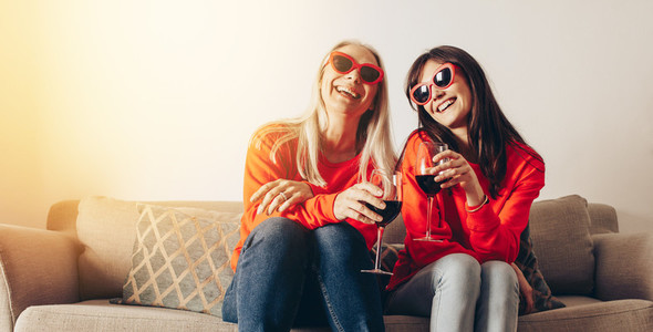 Smiling mother and daughter having fun at home drinking wine