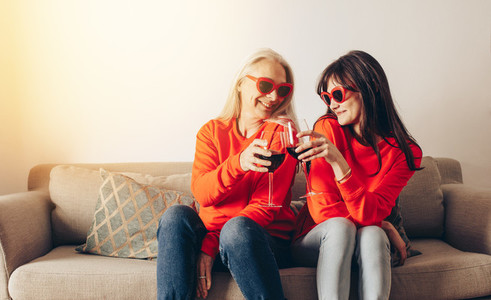 Mother and daughter enjoying wine sitting on couch at home