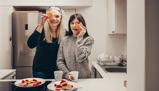 Smiling women standing in kitchen holding cookies