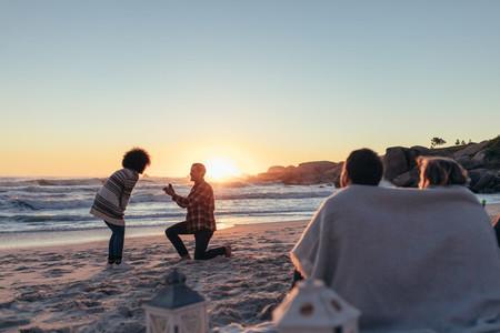Man proposing to his girlfriend at sea shore