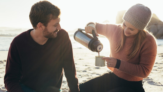 Beautiful young couple having coffee at the beach