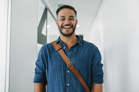 Happy young man in office corridor