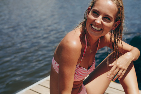 Smiling woman on a holiday relaxing near a lake