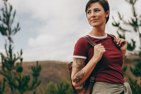 Woman hiker carrying a backpack looking away