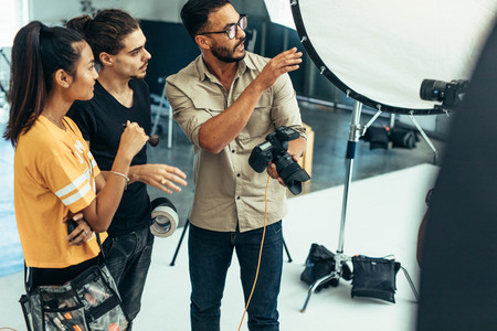 Photographer working with his team during a photo shoot in a stu