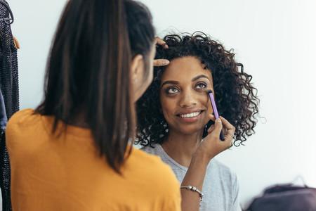 makeup artist applying makeup under the eye of a model