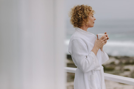 Woman enjoying coffee standing in the balcony of a beach house