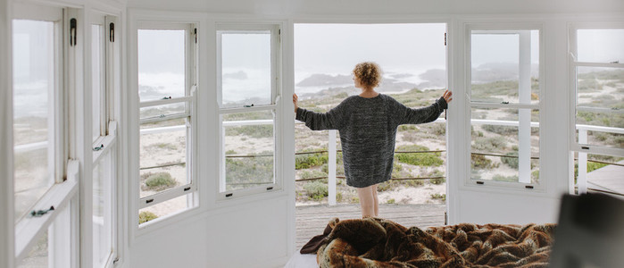 Rear view of a woman looking out of a beach house
