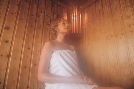 Woman sitting in a wooden sauna spa taking steam bath