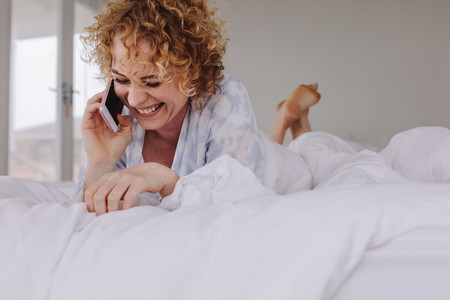 Woman talking over mobile phone lying on bed