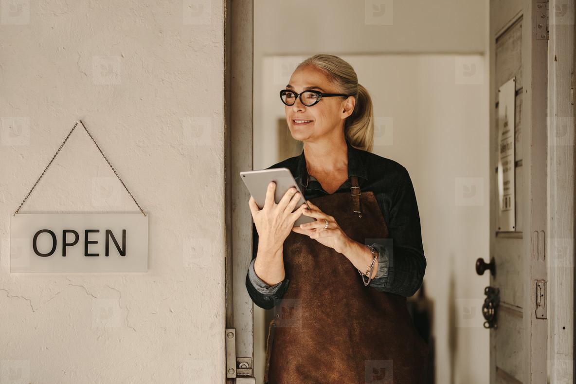 Goldsmith at workshop entrance with digital tablet