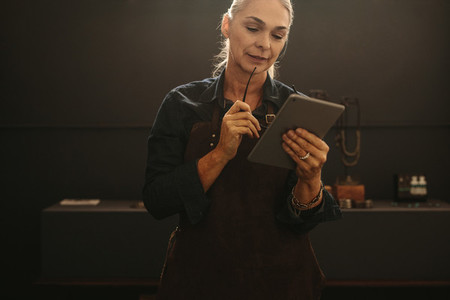 Senior female goldsmith using digital tablet