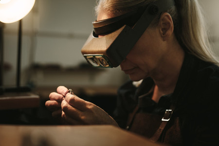 Senior jeweler examining a ring with magnifying glass