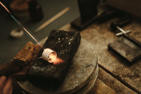 Jeweler solders a metal ring
