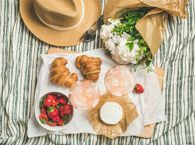 Flat lay of glasses of rose wine strawberries croissants brie cheese