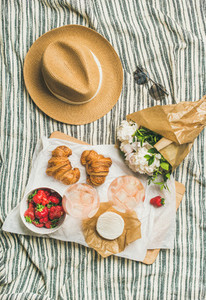Flat lay of rose wine  strawberries  croissants  brie cheese  peony flowers