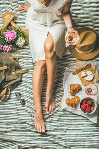 Girl in dress sitting on blanket with wine and snacks