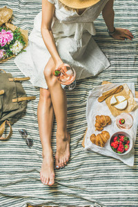 Woman in white dress sitting with wine and snacks