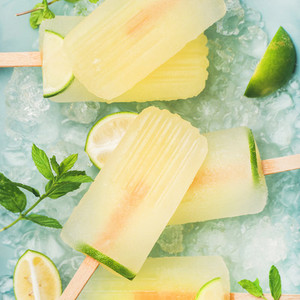Summer lemonade popsicles with lime and chipped ice square crop