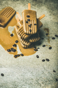 Flatlay of melting coffee latte popsicles with beans  copy space