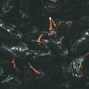 Flat lay of black dried raisins  selective focus  close up