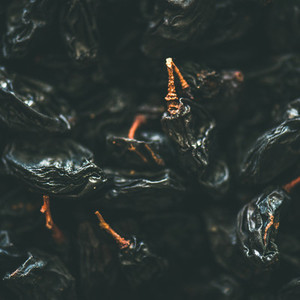 Flat lay of black dried raisins  selective focus  close up