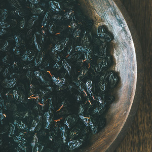 Black dried raisins in plate over wooden background square crop