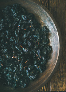 Black dried raisins in vintage plate over rustic wooden background