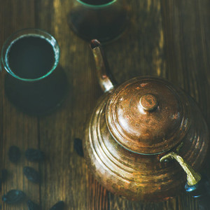 Oriental teapot  black tea in glasses and raisins  square crop