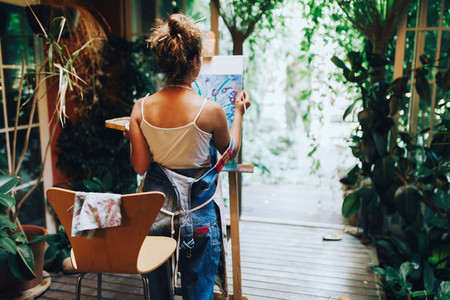 Woman painter painting in canvas
