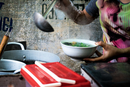 Woman pouring soup in a bowl