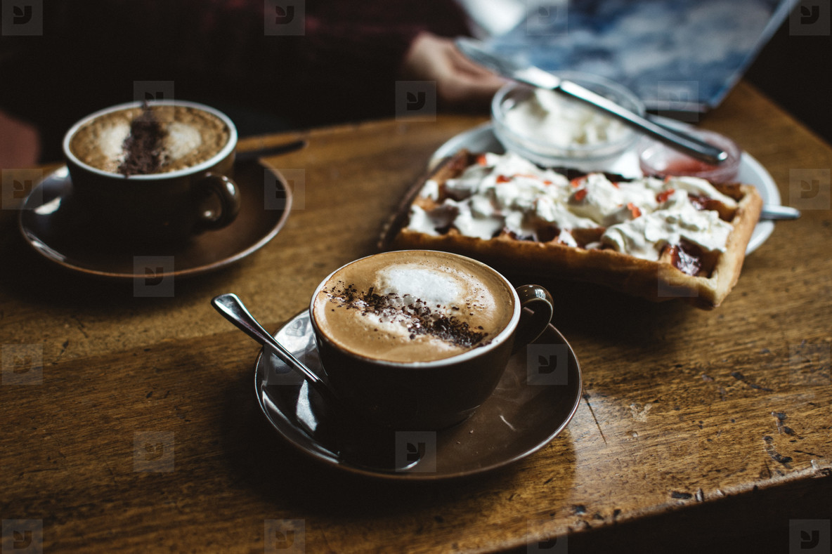 Wooden desk with two cappuccinos