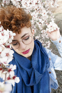 Young redhead woman surrounded by flowers