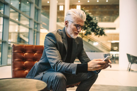 Senior executive using phone in office lobby