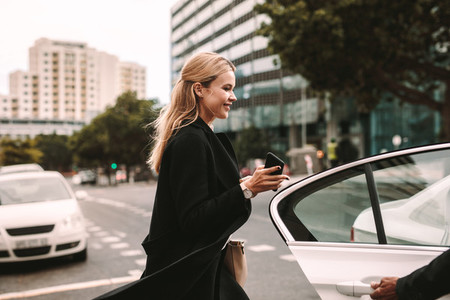 Smiling businesswoman getting into a taxi