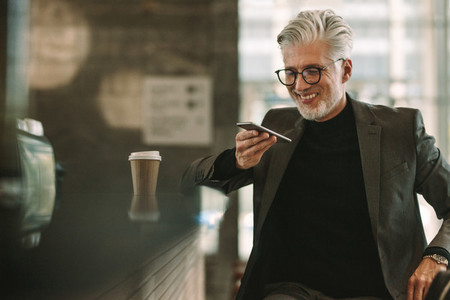 Smiling businessman at cafe making phone call