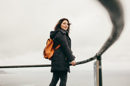 Traveling woman standing at the railing on mountain top