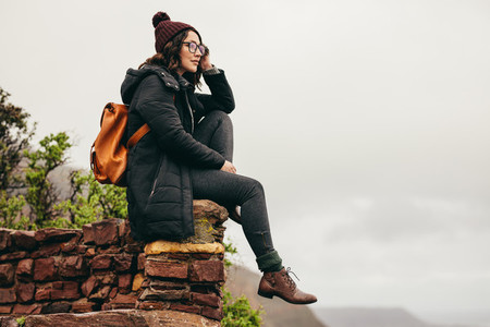 Woman traveler on mountain contemplating the view
