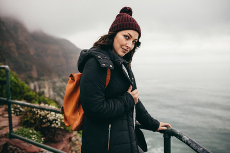 Female tourist standing by a mountain top railing