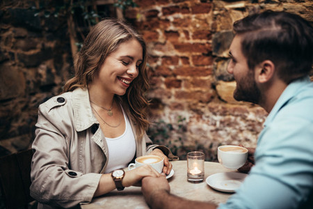 Couple in love holding hands and talking at a restaurant table
