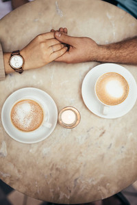 Hands of couple together on a coffee table