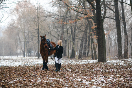 Young woman with horse in snow